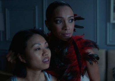 Woman wearing a feather boa holding another woman's head by her hair