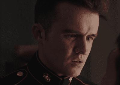 Man in military uniform standing in a dark room
