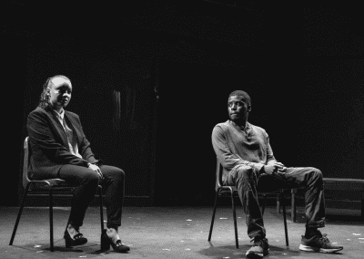 Man and woman sitting on stage in a theatre