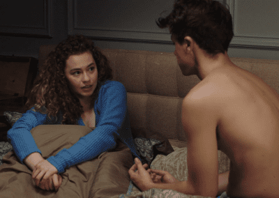 Shirtless man talking to a woman while sat on a bed