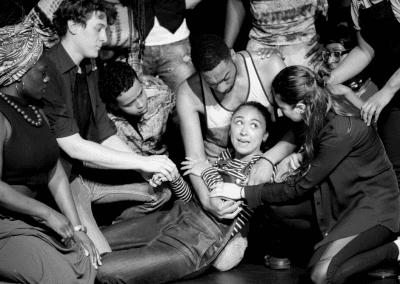Group of people gathered around a woman who is lying on the floor