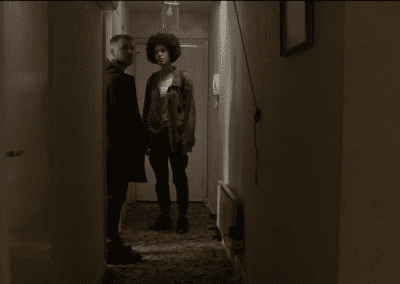 Man and woman standing at the end of a long narrow hallway